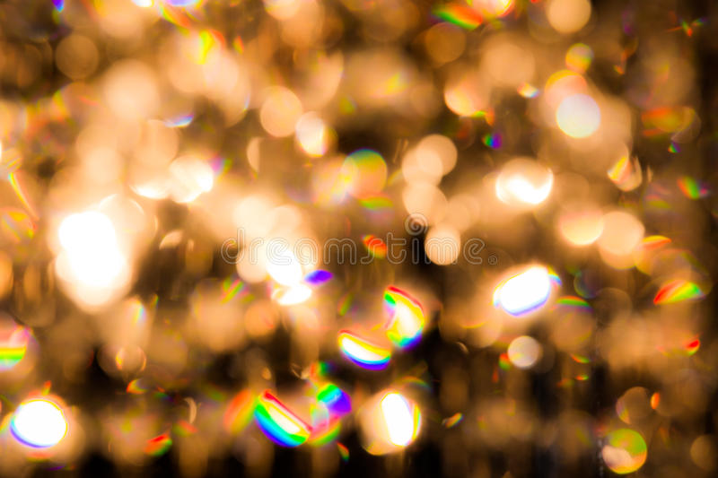 A crystal chandelier shines with golden light. Background created by a crystal chandelier that shines with golden light royalty free stock photography