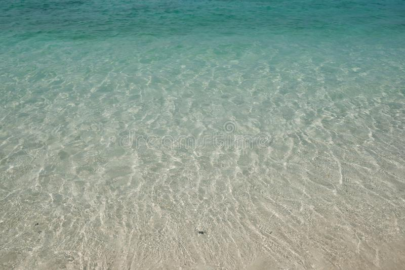 Crystal clear Andaman blue sea with smooth curve of water and sand beach beneath it. In bright daylight stock image