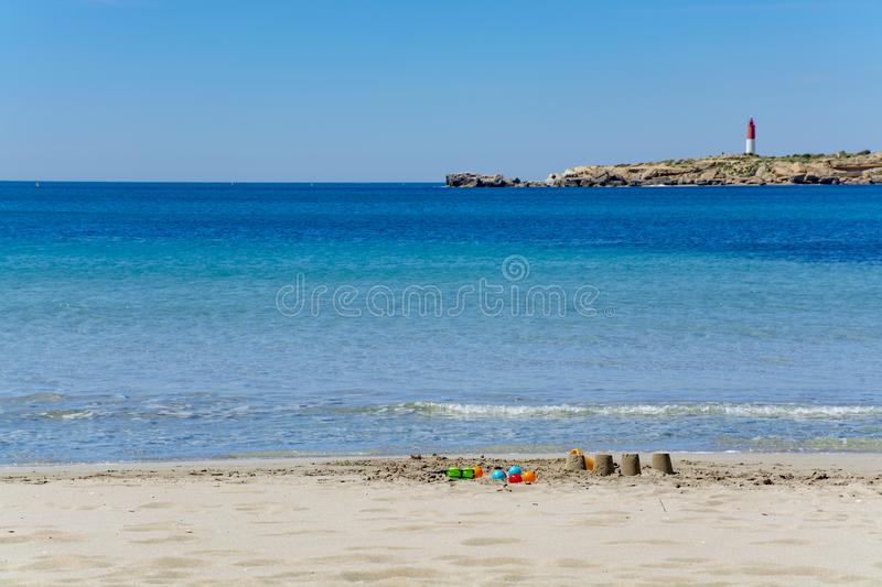 Crystal clear blue Mediterranean sea water on St.Croix Martigues beach and kids beach toys, Provence, France. Crystal clear blue water of  Mediterranean sea on stock photography