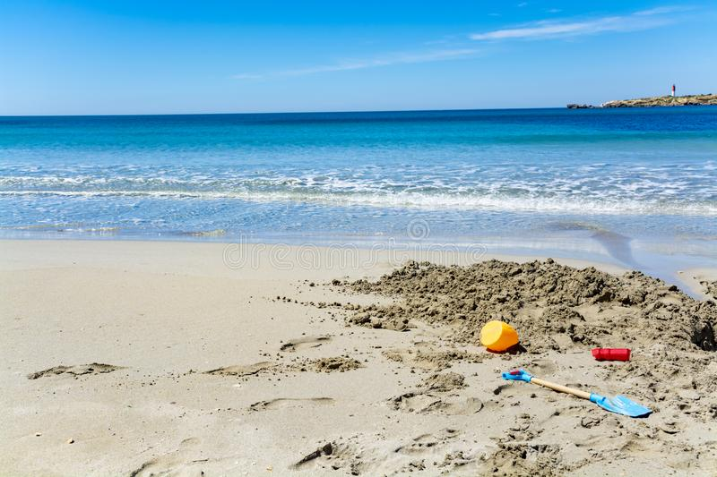 Crystal clear blue Mediterranean sea water on St.Croix Martigues beach and kids beach toys, Provence, France. Crystal clear blue water of  Mediterranean sea on stock photo