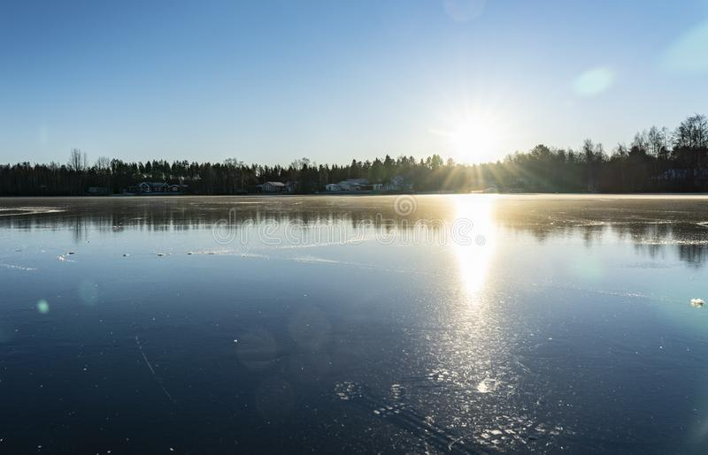 Crystal clear frozen lake in Northern Sweden - ice like big mirror. Low sun lights with warm light at very cold winter day royalty free stock photography