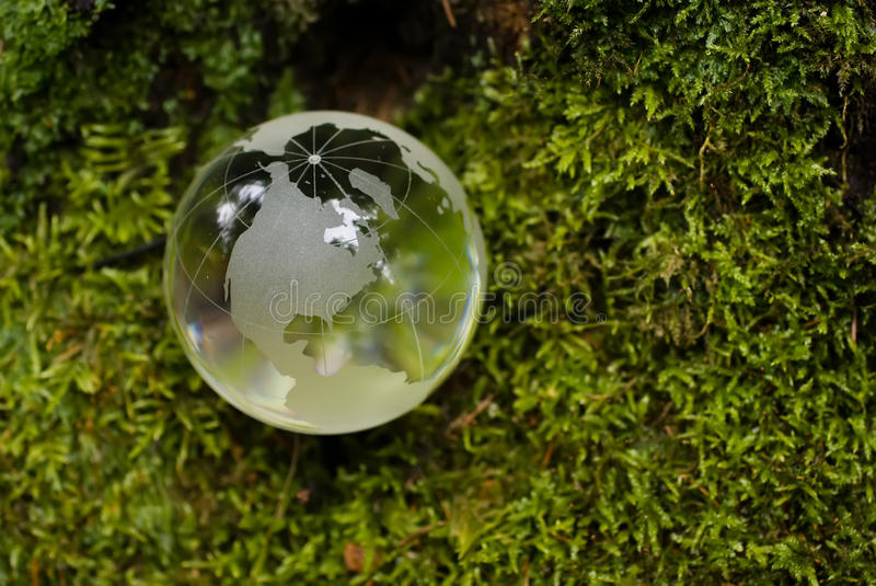 Crystal-clear globe on green moss. Crystal-clear globe on the background of the clean green moss symbolizes attention to ecology stock photos