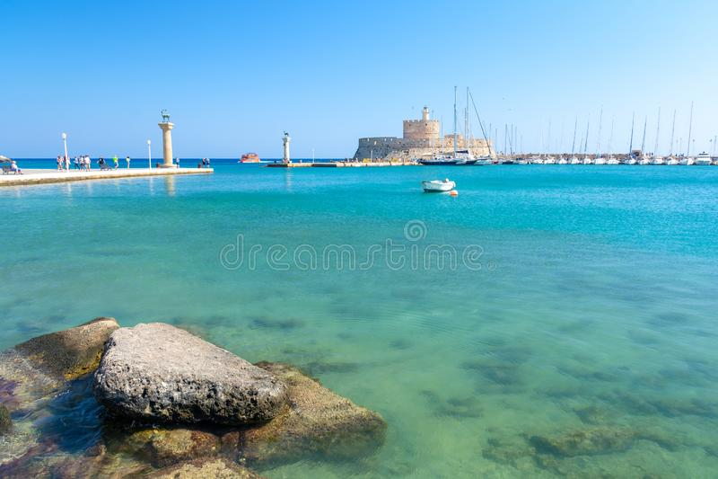Crystal clear sea in Mandraki harbour in Rhodes town, Greece. Beautiful sea and architecture of greek town Rhodes royalty free stock photo