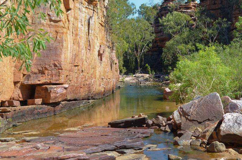 Steep Red Cliff Face. Crystal clear stream flowing past the steep red cliff face in Umbrawarra Gorge in the NT, Australia royalty free stock photos