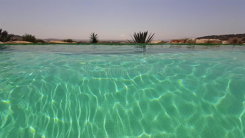 Transparent and crystal clear water with sun reflections in an infinity pool. royalty free stock image