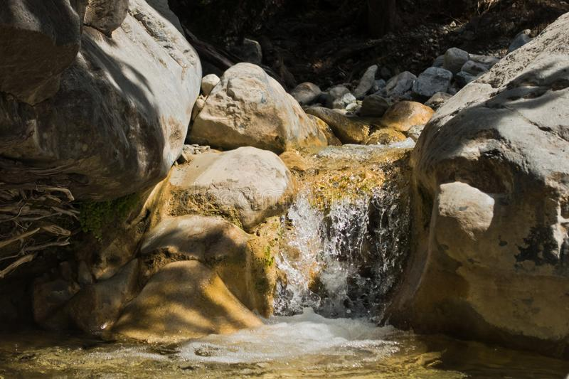 Crystal clear water of a cold mountain creek at rocky terrain of Samaria gorge, south west part of Crete island royalty free stock photo