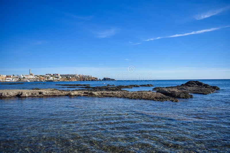 Crystal clear water envelop dark grey rocks. That just rise above the surface, with the small village of Cabo de Palos, Spain in the background stock photo
