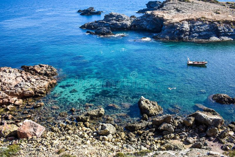 Crystal clear water envelop dark grey rocks with snorkelers. Crystal clear water envelop dark grey rocks that just rise above the surface, with a small boat and royalty free stock image