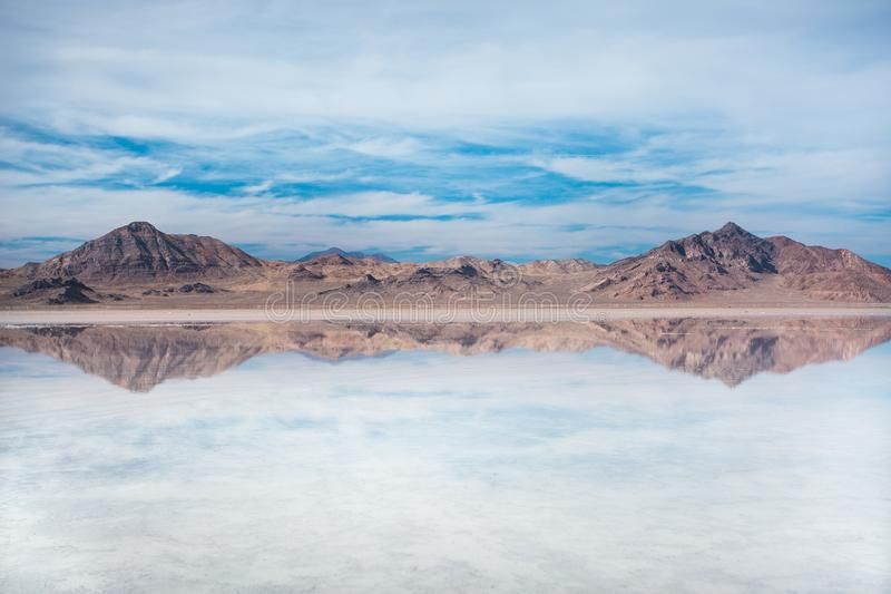 Bonneville Salt Flats, Tooele County, Utah, United States. Crystal clear water with mountains and blue, cloudy sky. Bonneville Salt Flats, Tooele County, Utah royalty free stock images
