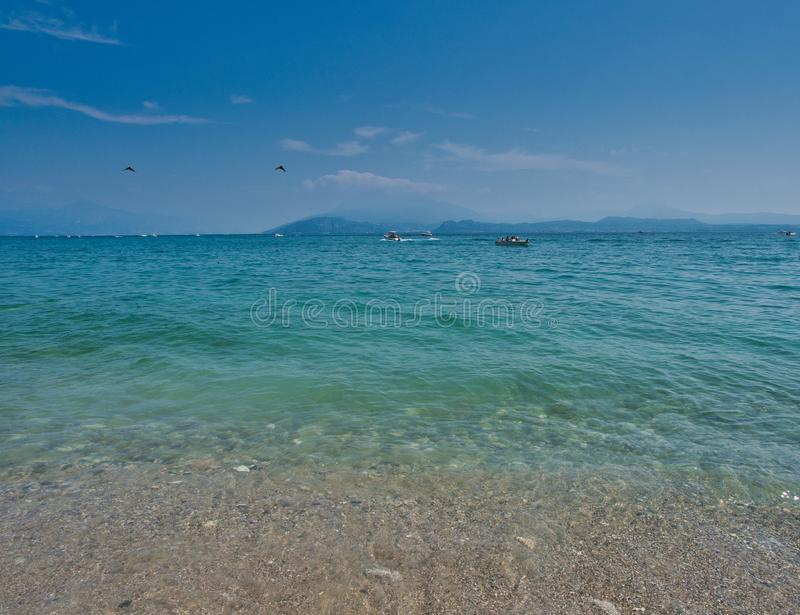 Crystal clear waters of Lake Garda on the banks of the village of Sirmione. Sirmione, Lombardy / Italy - July 07, 2019 Crystal clear waters of Lake Garda on the royalty free stock photography