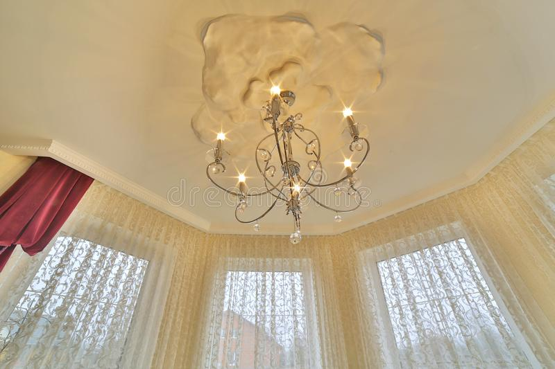 Crystal of contemporary chandelier, is a branched ornamental light fixture designed to be mounted on ceilings or walls royalty free stock photo