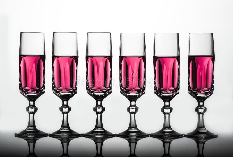Crystal exponeringsglas med rosa vätska arkivfoton