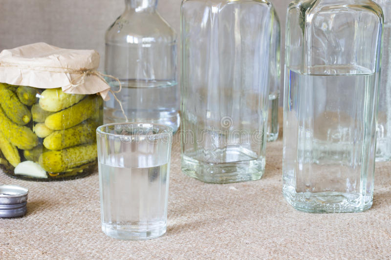 Crystal glass and bottle and pickled cucumber on sacking stock images