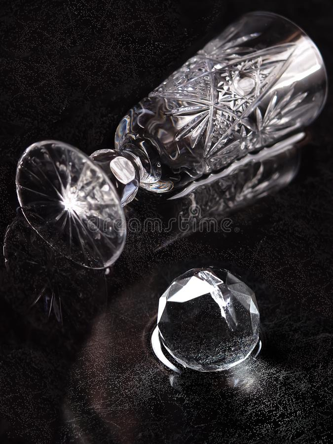 A crystal glass and a crystal ball lie on a table flooded with water. On a black background royalty free stock photos