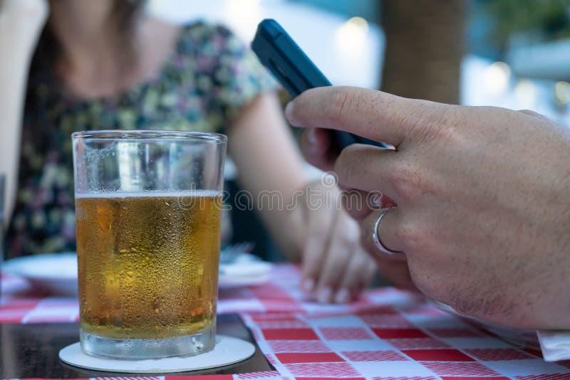 Crystal Glass de refrescar cerveja e marido com sua esposa em um bar Lager em um terraço de bar com companhia e conversando por imagem de stock royalty free