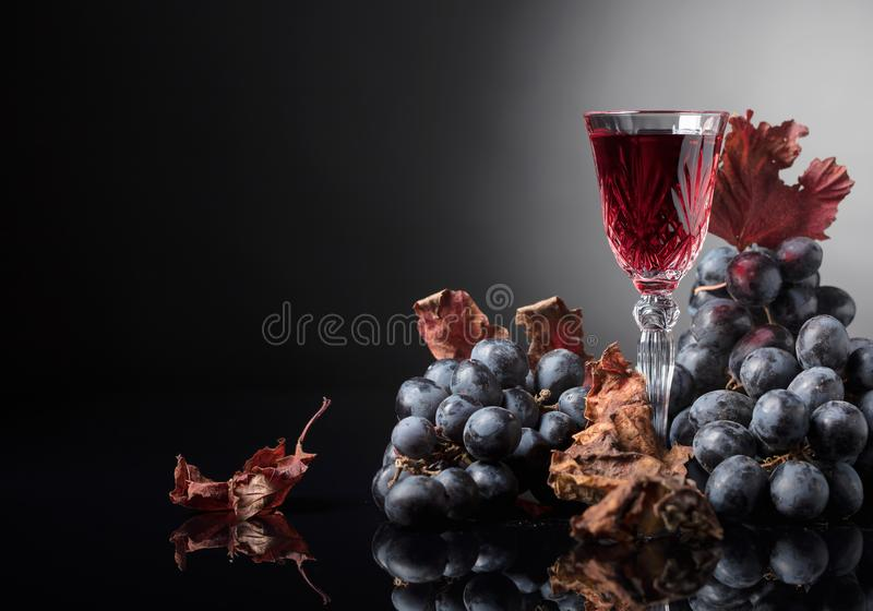 Crystal glass of red wine and grapes with dried vine leaves. royalty free stock images