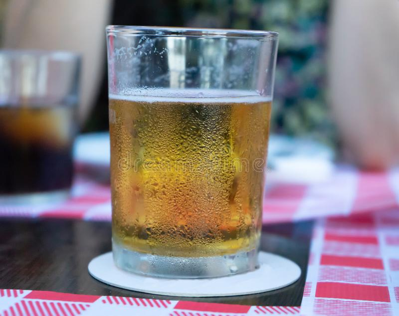 Crystal Glass of refreshing draft beer with a friend in a table of a pub. Lager in a bar terrace with company. Thirsty drunk. Person drinking alcohol in stock photos