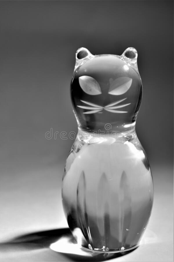 Crystal glass sitting cat with whiskers figurine. Black and white stock photography