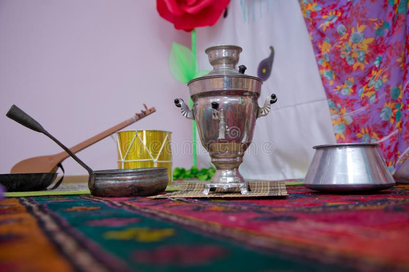 Crystal glass of tea on with metal samovar . cast iron old pot . Iron Wok very old . Azerbaijan tea samovar Concept traditional stock photography