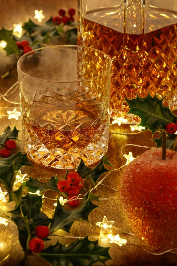 Crystal glass of whisky and a whisky decanter with christmas lights, baubles and holly berries royalty free stock photo