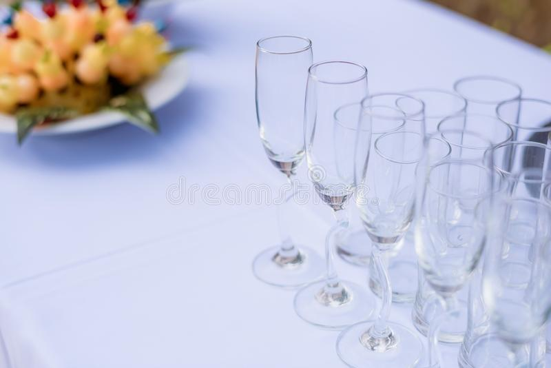 Crystal glasses of champagne on the wedding Reception table. Table setting for an event party or wedding reception at the beach. stock photos