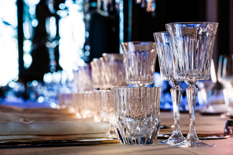 Crystal glasses, table restaurant holiday background. Classic. Cutlery and glasses on a long table ready for dinner or lunch. Endless background luxury with royalty free stock photo
