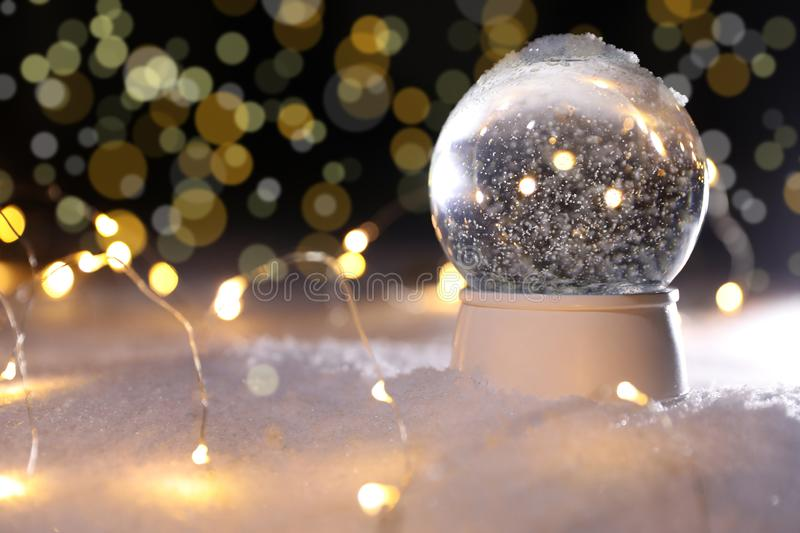 Crystal globe and Christmas lights on snow against blurred background, space for text. Winter decor royalty free stock images