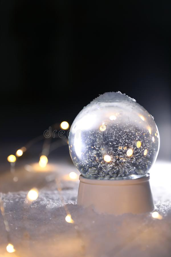 Crystal globe and Christmas lights. On white snow outdoors royalty free stock images