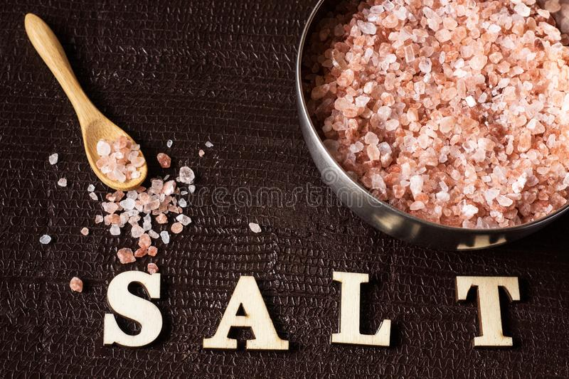 Crystal himalayan salt in metal bowl with wooden spoon royalty free stock images