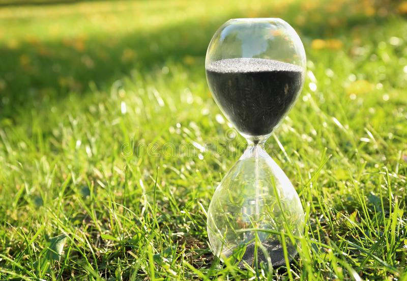 Crystal hourglass with black sand on green grass outdoors stock image
