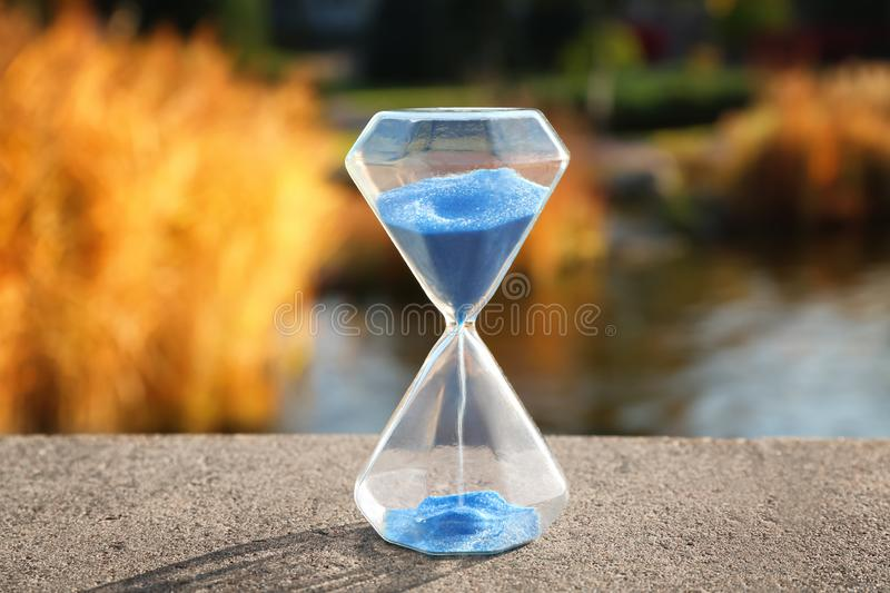 Crystal hourglass with blue sand outdoors royalty free stock photography