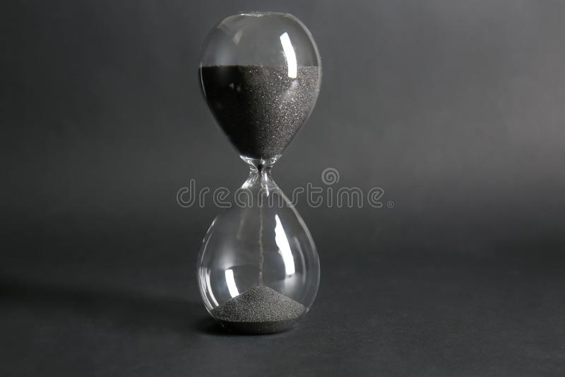 Crystal hourglass on dark background stock photo