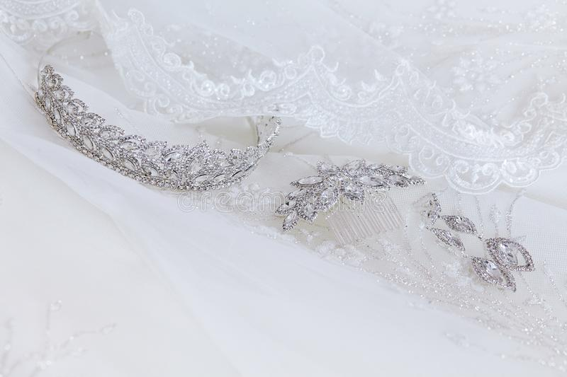 Crystal jewellery: earrings, hairpin, diadem on a white wedding background. royalty free stock photography