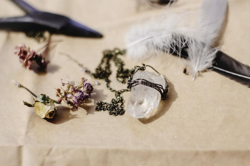 Crystal necklace, feather, and dried flowers on craft background stock photo