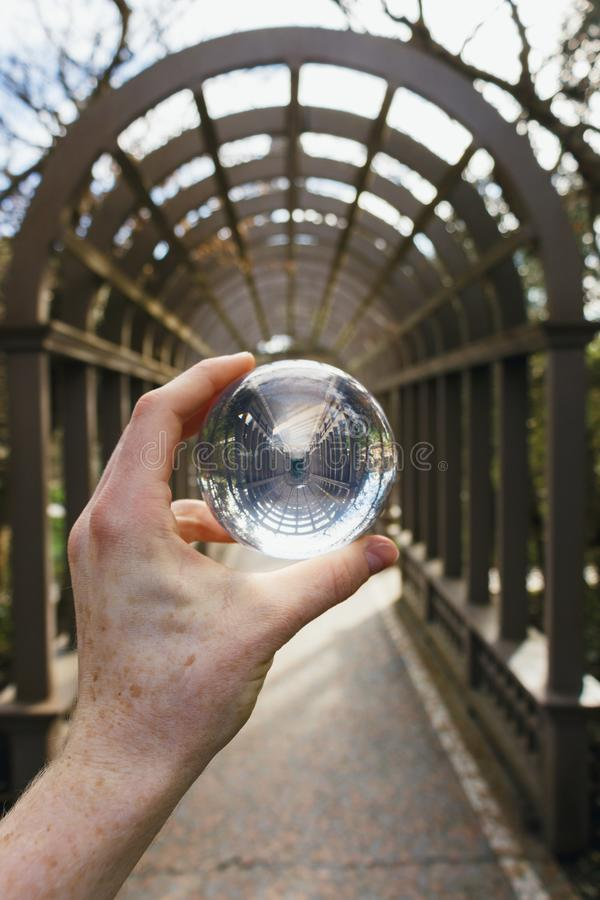 A crystal sphere held up in a garden stock photography