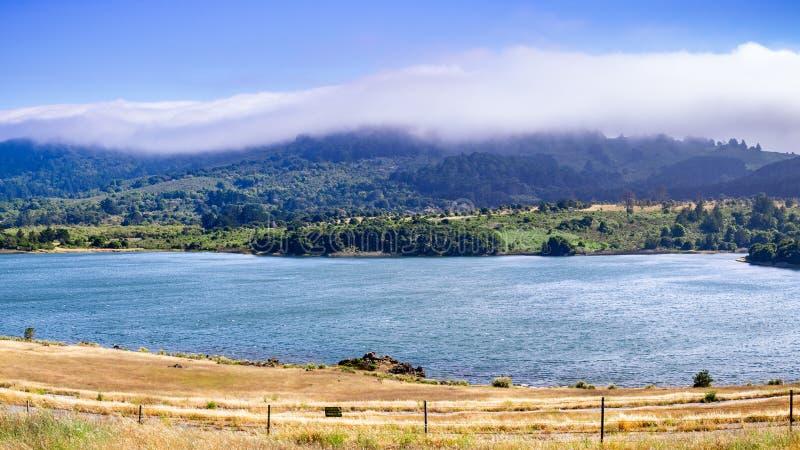 Crystal Springs Reservoir superiore, la parte dello spartiacque di San Mateo Creek e le montagne di Santa Cruz hanno coperto di n fotografia stock