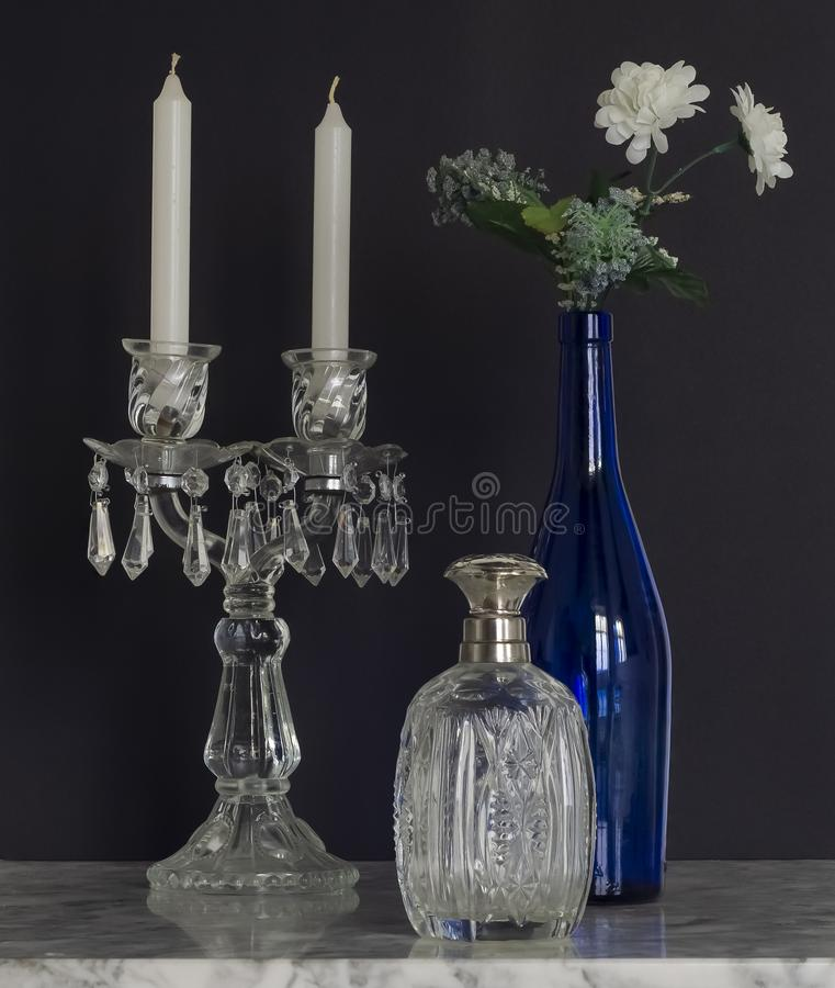 Crystal Table Chandelier with Blue glass Bottle and Flowers Still stock image