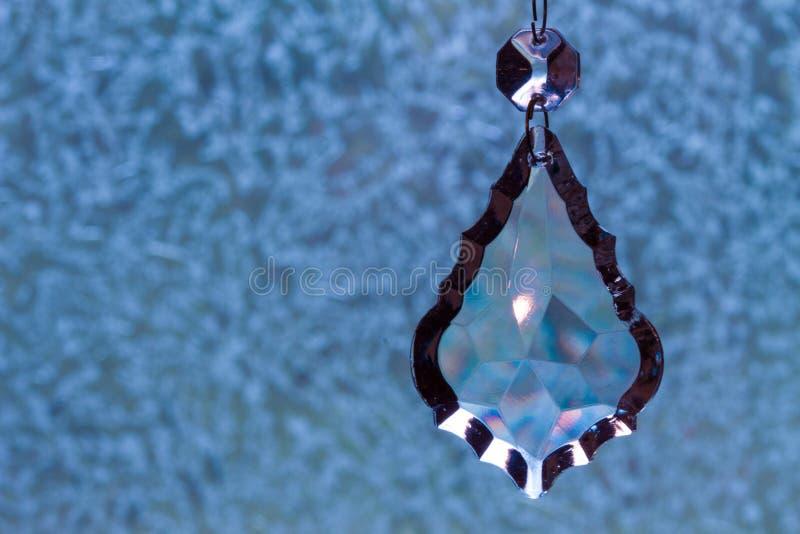 Crystal Teardrop Pendant, colgando contra fondo azul imagen de archivo