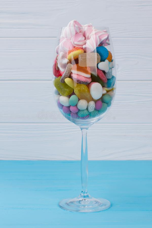 Crystal wine glass with colorful candies. royalty free stock images