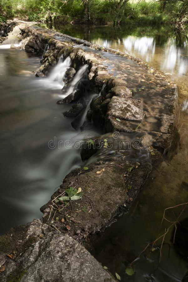 Detail of small dam built of stone. Crystalline water that flows through the stones of a small dam built by Man, forming small waterfalls stock photos