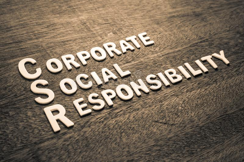CSR Wood Letters Corporate Social Responsibility. CSR abbreviation with text Corporate Social Responsibility by wood letters on wood background stock photo