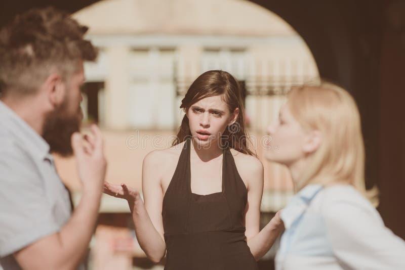 Cuál es su problema Conflicto en la relación romántica que implica a tres personas Mujer celosa que culpa al hombre desleal por imagen de archivo libre de regalías