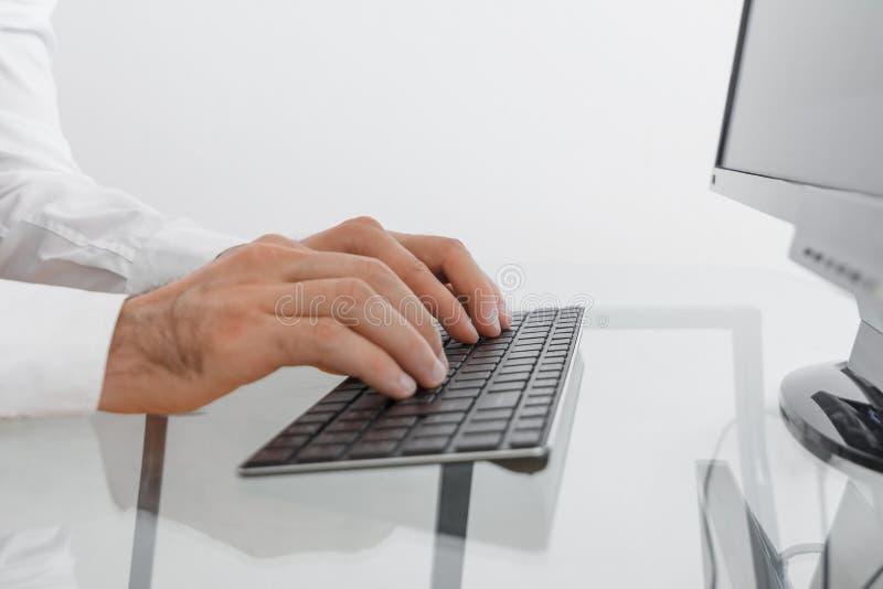 Cuídese en una capa médica blanca que mecanografía en un teclado negro El hombre de negocios en una camisa blanca está escribiend foto de archivo libre de regalías