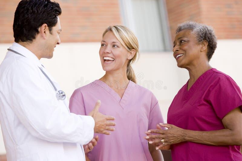 Cuídese y las enfermeras que se colocan fuera de un hospital foto de archivo libre de regalías