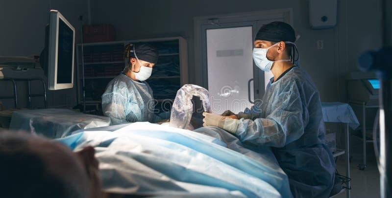Cuídese y un ayudante en la sala de operaciones para la clínica quirúrgica fotografía de archivo