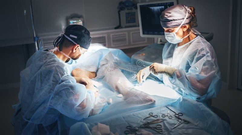 Cuídese y un ayudante en la sala de operaciones para la clínica quirúrgica fotos de archivo