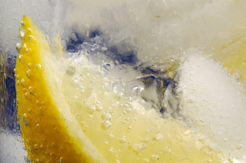 Cuña de limón en el agua mineral de cristal con hielo foto de archivo