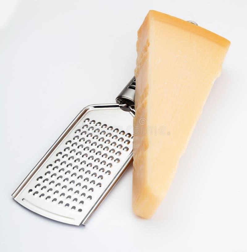 Cuña del queso parmesano o del grana con el rallador fotografía de archivo