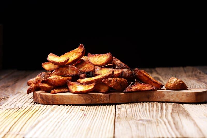 Cuñas cocidas al horno de la patata la patata vegetariana del vegano vegetal orgánico hecho en casa acuña los snacks imagen de archivo
