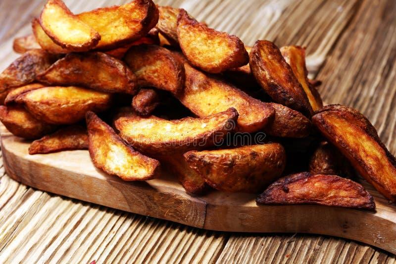 Cuñas cocidas al horno de la patata la patata vegetariana del vegano vegetal orgánico hecho en casa acuña los snacks imágenes de archivo libres de regalías